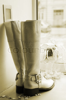 Women's leather boots against the window