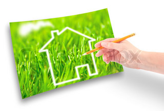 Hand of a girl with a pencil draws a house against on the green grass