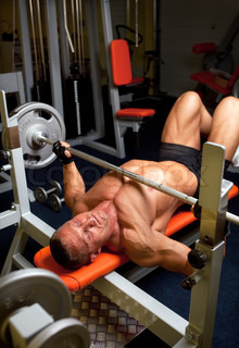 Muscular man with dumbbell in home fitness