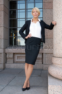 Young businesswoman leaning to colonnade pillar, looking at camera