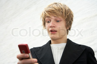 Teenage boy looking at mobile phone by building wall, surprised expression