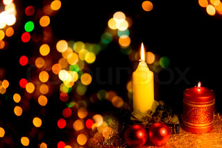 Burning candle with Christmas-tree decorations on a dark background