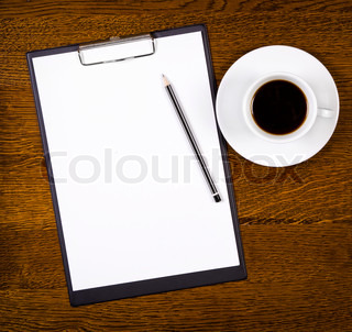 Clipboard with blank page and cup of coffee on wooden desk View from above