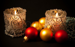 Two candles in glass candlesticks with christmas-tree decorations on black background