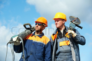 Two Builder workers with pneumatic hammer and grinding machine equipment over blue sky