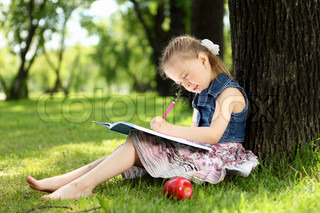 Portrait of a little girl sitting and reading on the grass in the park