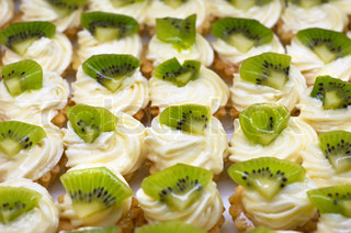 Small cakes petit four with custard and kiwi on top. Shallow DOF. Sharp focus on second line.