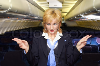 air hostess gesturing in the empty airliner cabin