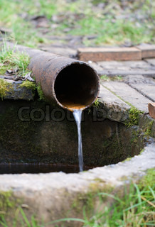 On a rusty pipe water in a well flows down