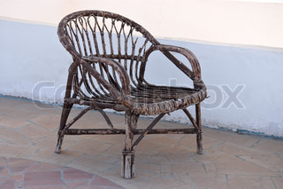 Old wicker chair against white wall background