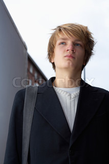Portrait of teenage boy in street, low angle view