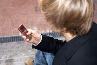 Teenager SMS mit Handy, high-angle view