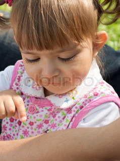 Little girl looking with interest on an ant