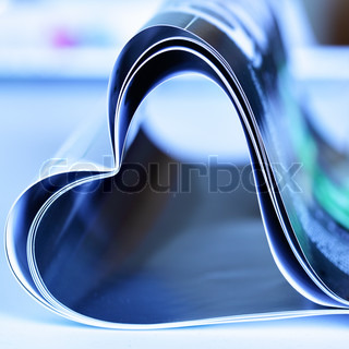 Magazine folded to heart shape over white background
