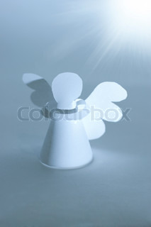 Handmade angel cut out from  paper at bright star lighting. Religion concept.