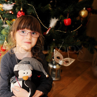 Close-up portrait of smiling little girl sitting with a toy under Christmas tree