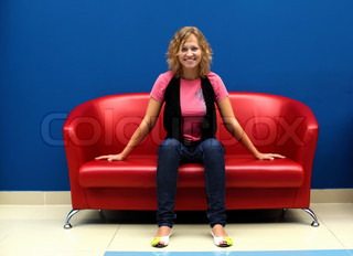 Portrait of young woman sitting on red sofa against blue wall