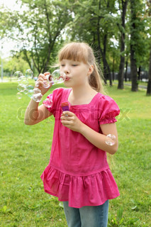 Little girl in the summer park blowing bubbles