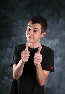 Young teen boy showing both thumbs up on a mottled background