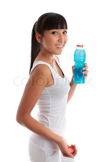 Fit healthy girl holding a bottle of drink after exercise or workout