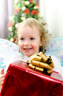 little girl smiling with christmas gift in hand