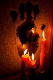 Horror (three candles burning in the darkness and lighting a frozen window with a black handprint)
