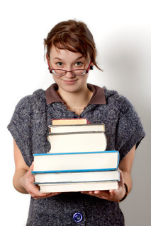 Photo of young girl studying with books