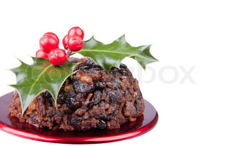 Traditional Christmas fruit pudding decorated with holly