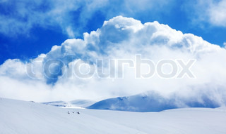 Winter landscape of high mountains with snow blizzard and fresh blue sky, beautiful nature panoramic background