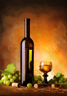 Still life with wine bottle, glass, grapes and vine leaves