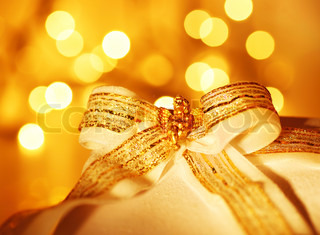 Gold holiday background with white present gift box, Christmas ornament and new year decoration over abstract defocused lights