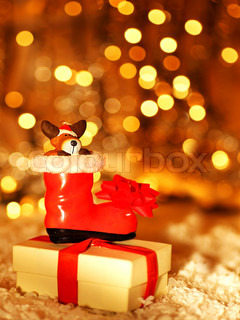 Holiday background with cute Santa boot Christmas tree decorative ornament & gift box in snow over abstract defocus lights
