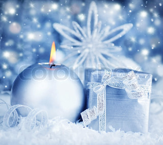 Winter holiday background with silver present gift box, candle ornament & Christmas snow decoration