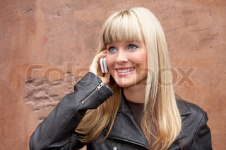 Portrait of young woman using mobile phone, smiling