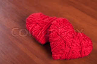 two red thread hearts closeup on wooden background