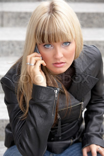 Young woman on mobile phone, looking at camera