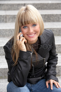 Young woman using mobile phone, looking at camera, smiling