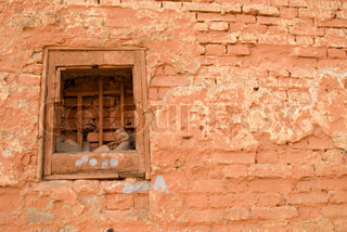 Red brick wall with a bricked-up window