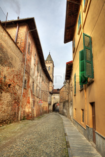 Vertical oriented image of narrow paved street among old historic houses in Saluzzo, northern Italy