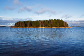 Small forest island on a lake in Finland, sunset
