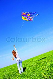 Girl playing with a kite on skyline