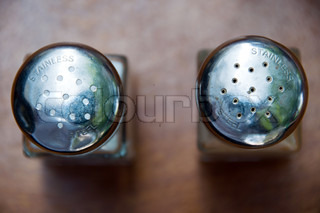 Top view on salt and pepper shakers with stainless steel imprint being placed on wooden table