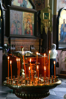 Candles and unidentified prayer standing in front of icon in Russian Orthodox Church in Jerusalem, Israel