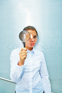 Young woman holding magnifying glass outside building