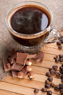 Cup of coffee, chocolate with nuts and coffee beans on wooden background with linen canvas