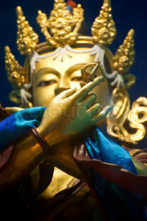 Golden Buddha sculpture in Tibetan Monastery. Focus on hand