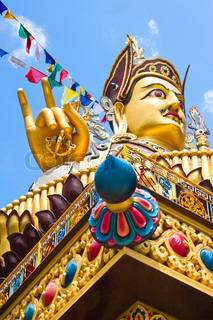 Golden Buddha sculpture in Tibetan monastery over blue sky with praying flags Focus on hand