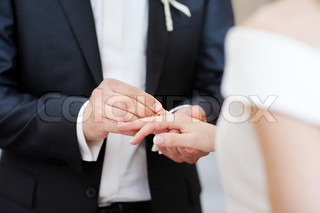 Groom putting a wedding ring on bride's finger