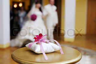 Two wedding rings on a decorated pillow