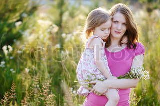 Young mother and her little girl in a meadow